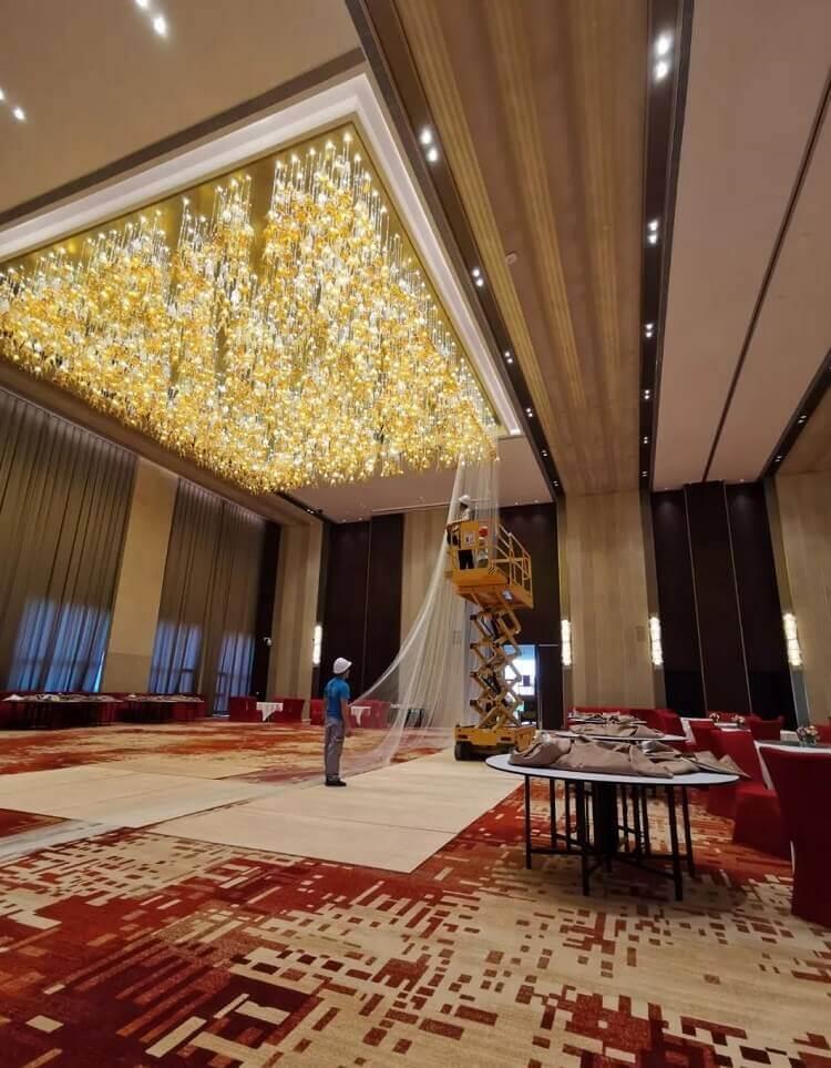Custom glass chandelier under installation in hotel banquet hall
